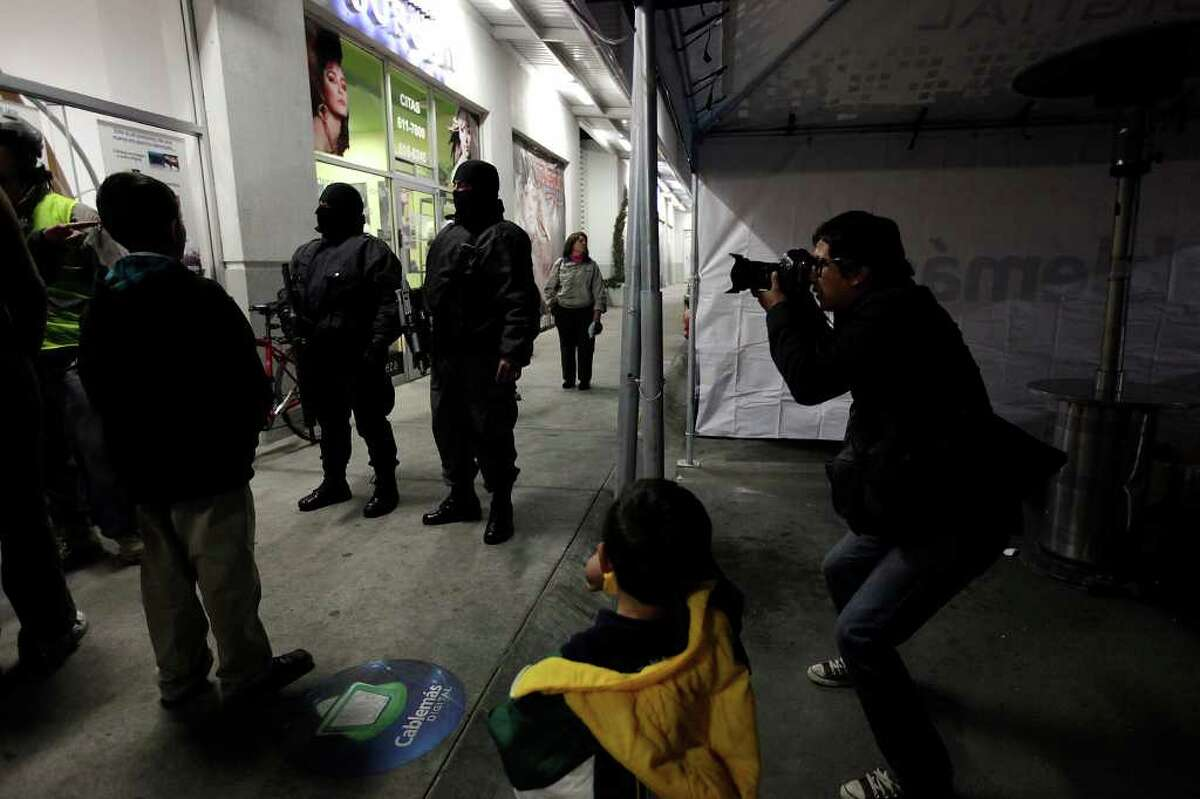 El Diario photojournalist Julio Cesar Aguilar covers the scene of a business dispute as police arrive to settle the problem in Ciudad Juárez.