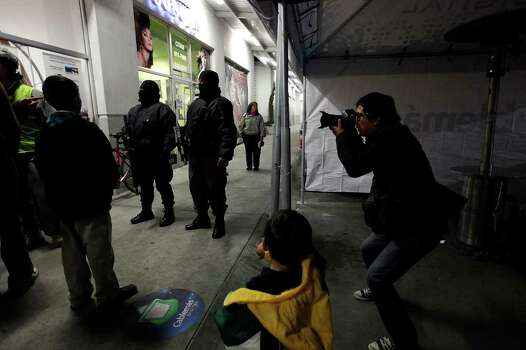 "MEXICO -- El Diario photojournalist Julio Cesar Aguilar covers the scene of a business dispute as Municipal Police arrive to settle the problem in Ciudad Juarez, Mexico, Friday, Dec. 3, 2010. Aguilar's coverage of the drug war in the city has earned a spot in an exhibit entitled, ""disquieting images,"" in Milan, Italy. He is exhibited besides photography legends as Diane Arbus, Eugene Richards,  James Nachtway and Mary Ellen Mark. JERRY LARA/glara@express-news.net Photo: JERRY LARA, San Antonio Express-News / glara@express-news.net"