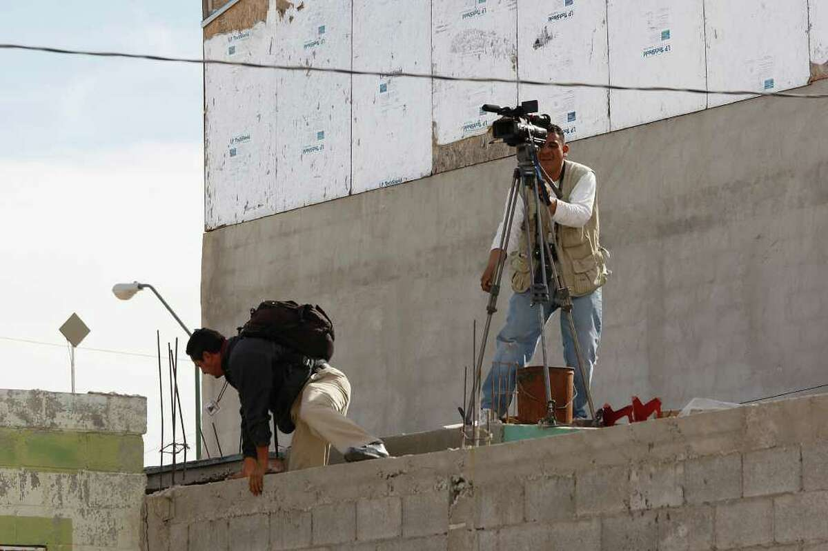 Media members find a vantage point after being driven from a scene where four police died in Ciudad Juárez, Mexico.