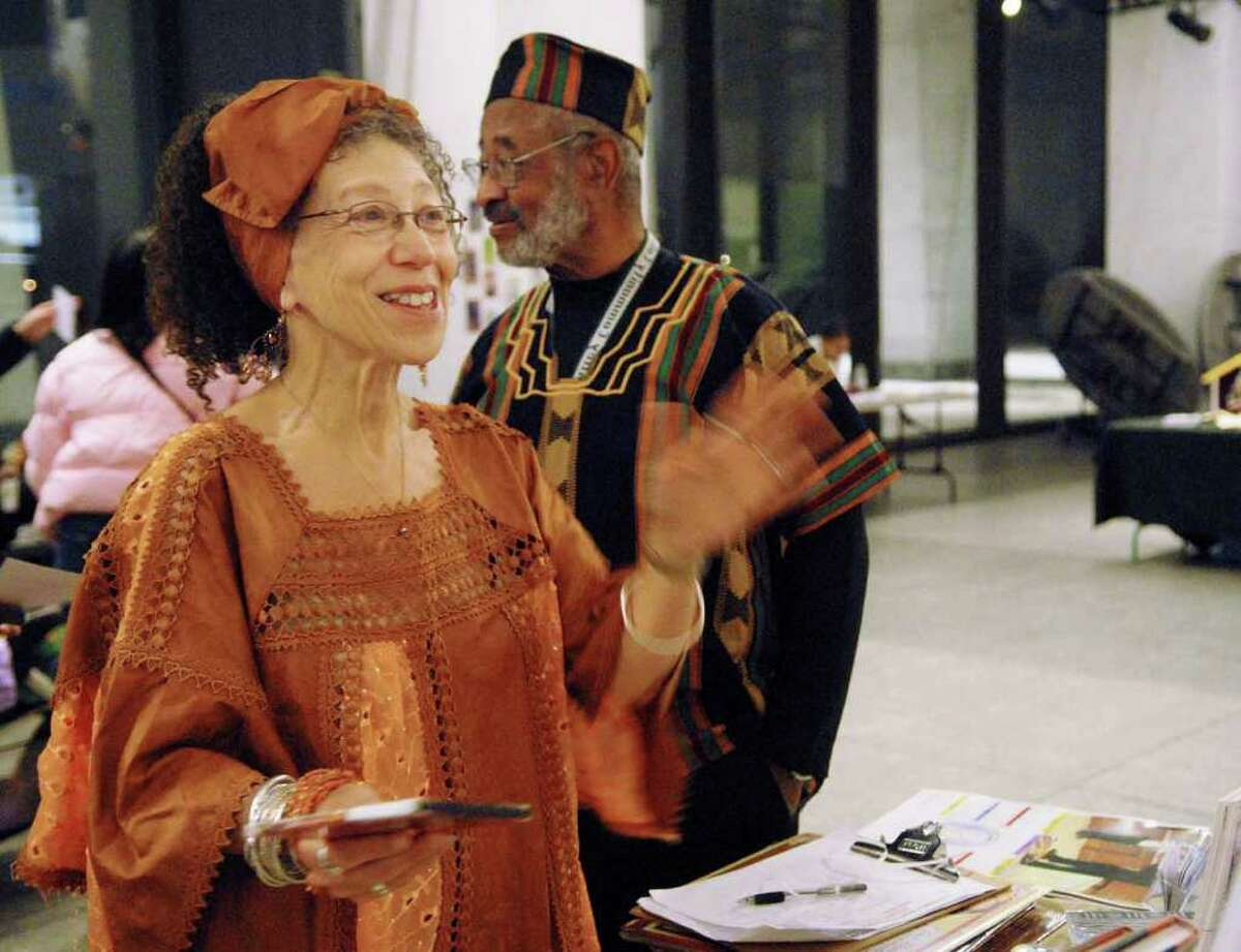Miki Cann, executive director of the Hamilton Hill Arts Center, talks to a vendor at the African Marketplace at the Capital Kwanzaa Celebration at the State Museum. (Luanne M. Ferris / Times Union )