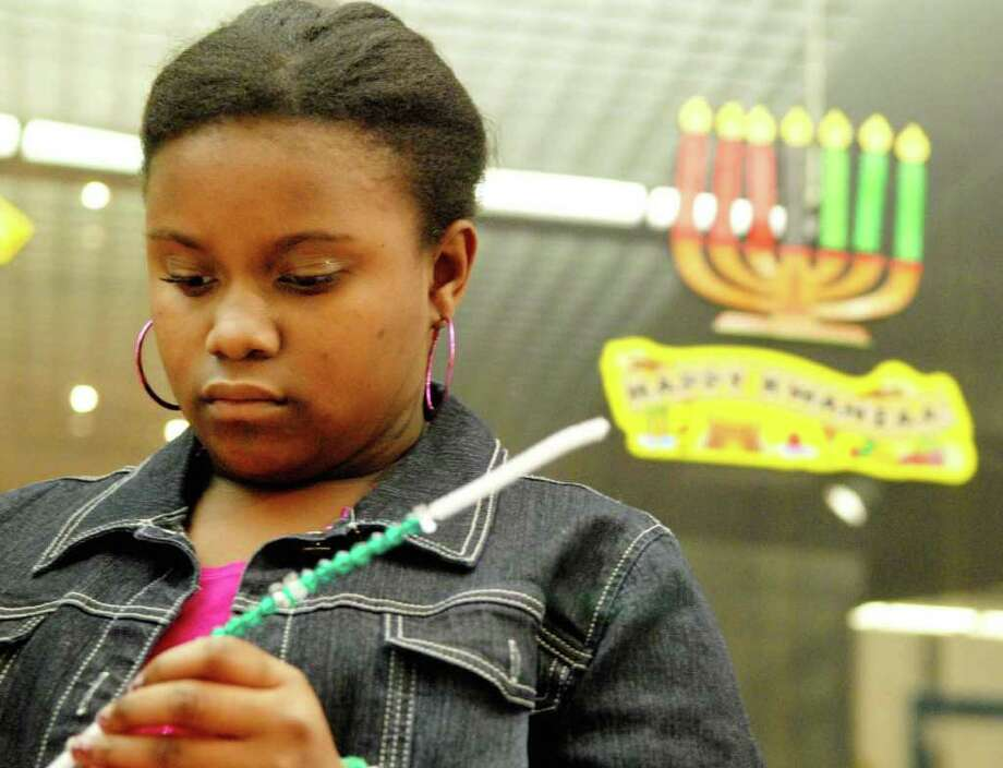 Naomi Shaw, 12, of Troy, makes a bracelet at the craft table at the 26th annual Capital Kwanzaa Celebration at the State Museum.  (Luanne M. Ferris / Times Union ) Photo: Luanne M. Ferris