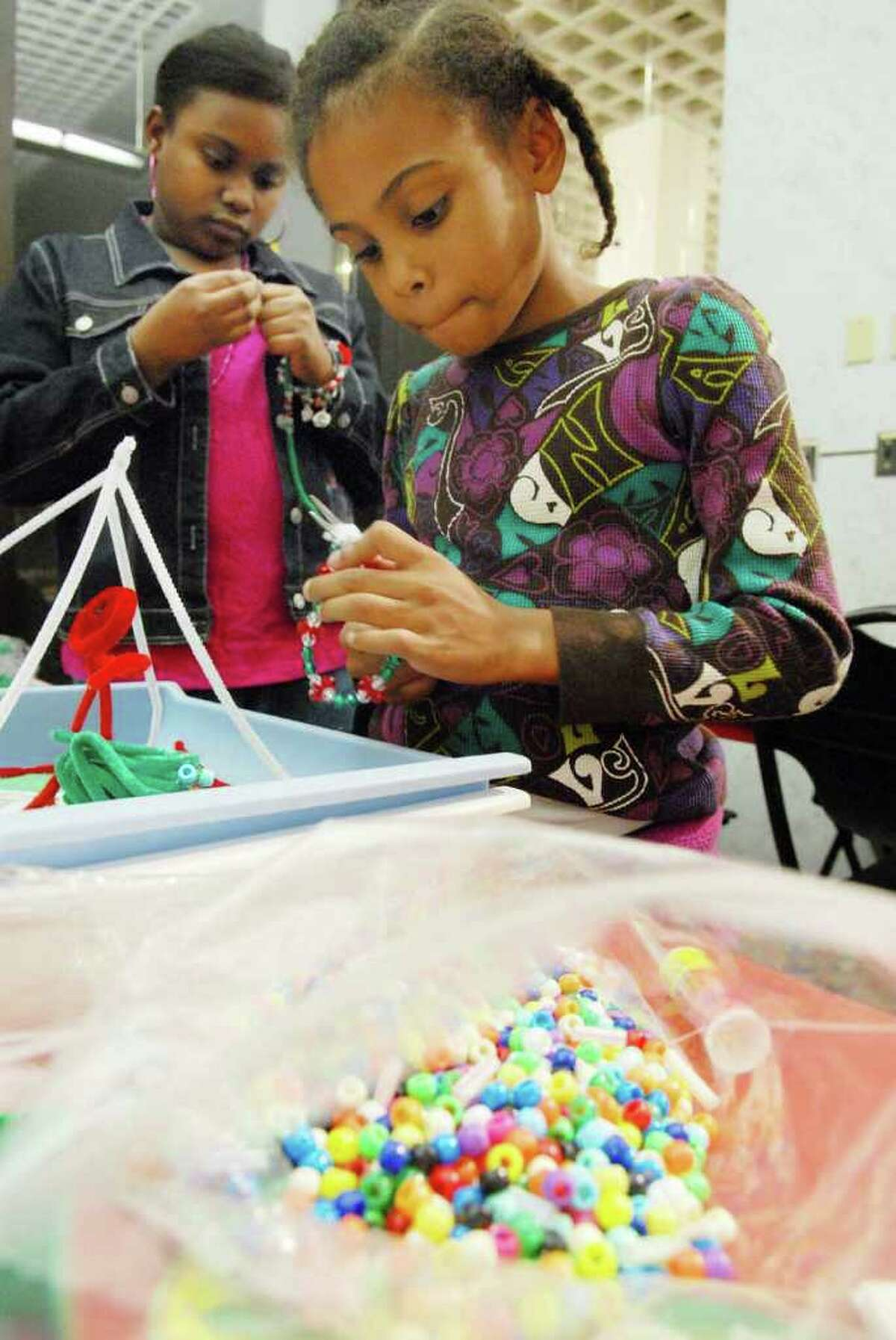 Naomi Shaw, 12, of Troy, left, and Elianna Jenkins-Taylor, visiting from Orlando, Fla., make bracelets at the craft table at the 26th annual Capital Kwanzaa Celebration at the State Museum. (Luanne M. Ferris / Times Union )