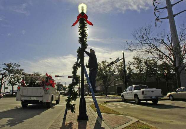 It's beginning to look not like Christmas, everywhere you go as city crews remove the street decorations around downtown.  Building and Maintenance employee Seburn Foux was on Main Street removing the green garland and red ribbons from the lamp posts after the holiday season.  Published on January 14, 2010. Dave Ryan/The Enterprise / Beaumont
