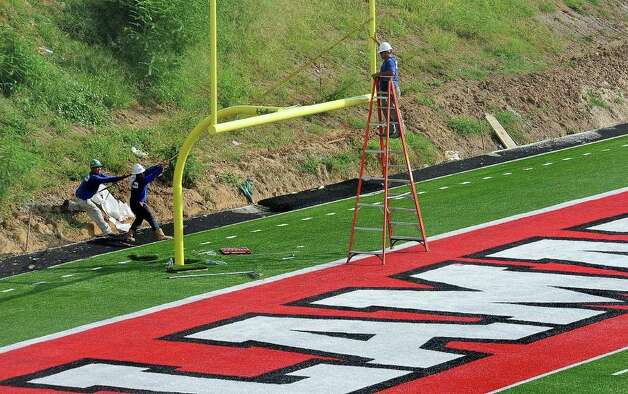 With Lamar's first home game nearing, workers align the goal posts on the north end of the Lamar Cardinal's refurbished football stadium. Published August 19, 2010  Guiseppe Barranco/The Enterprise / Beaumont