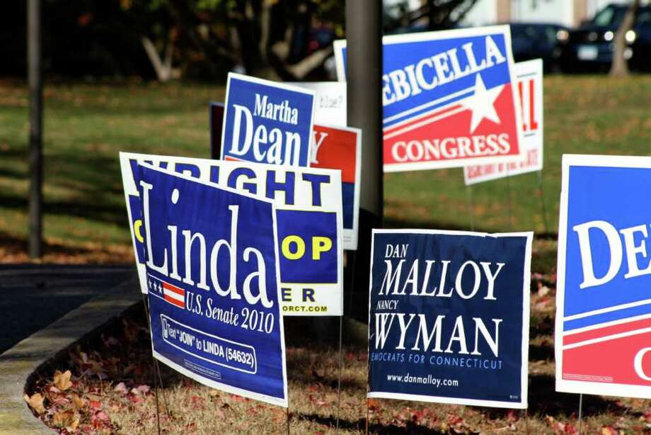 Numerous political signs cover the grass around Town Hall. Photo: Ben Holbrook Contributed Photo, Contributed Photo / Darien News