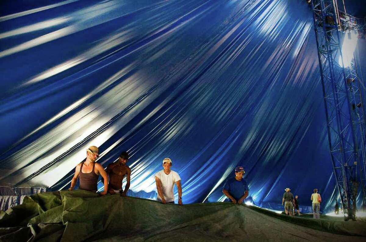 Crew members fold up a large tarp under the tent before raising the big top at the Big Apple Circus in Mill River Park in Stamford, Conn. on Tuesday July 6, 2010.
