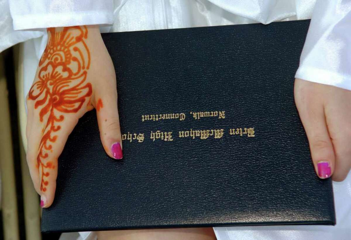 With a henna design on her hand, graduate Sarah Andersen holds onto her diploma in her lap, during Brien McMahon's 49th Commencement Exercises in Norwalk, Conn. on Tuesday June 29, 2010.