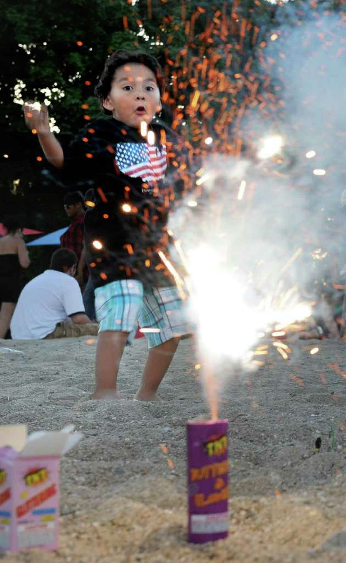 Brent Garcia, 4, reacts to a fountain firework lit by his father, Trini, at Calf Pasture Beach on Saturday, July 3, 2010.