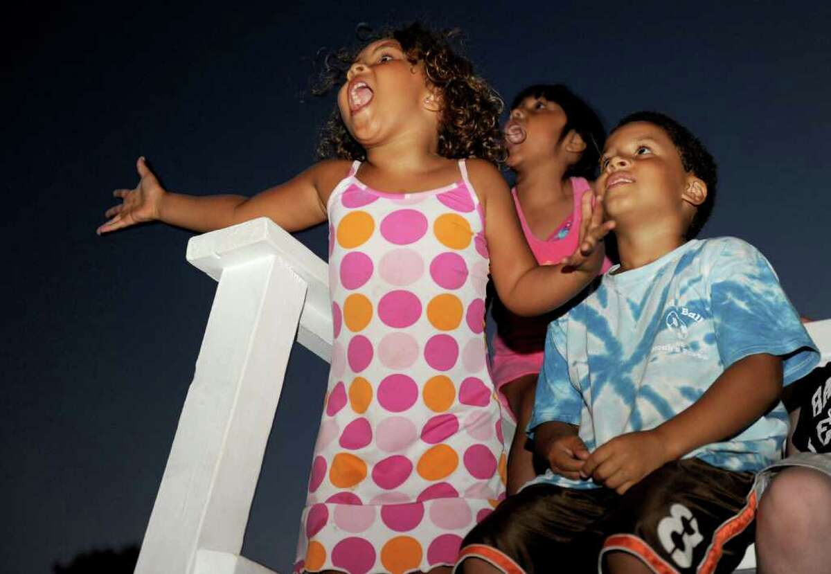 Sinead Roche, 5, left, and her brother Connor, 8, right, react to fireworks at Calf Pasture Beach on Saturday, July 3, 2010.