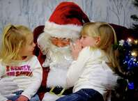 "Morgan Sylvia, 6, whispers what she wants for Christmas in Santa's ear as her sister, Darby, 3, listens during the Ludlowe Center for Health & Rehabilitation in Fairfield. The ""Pictures with Santa"" event was hosted by the Moms Club of Fairfield."