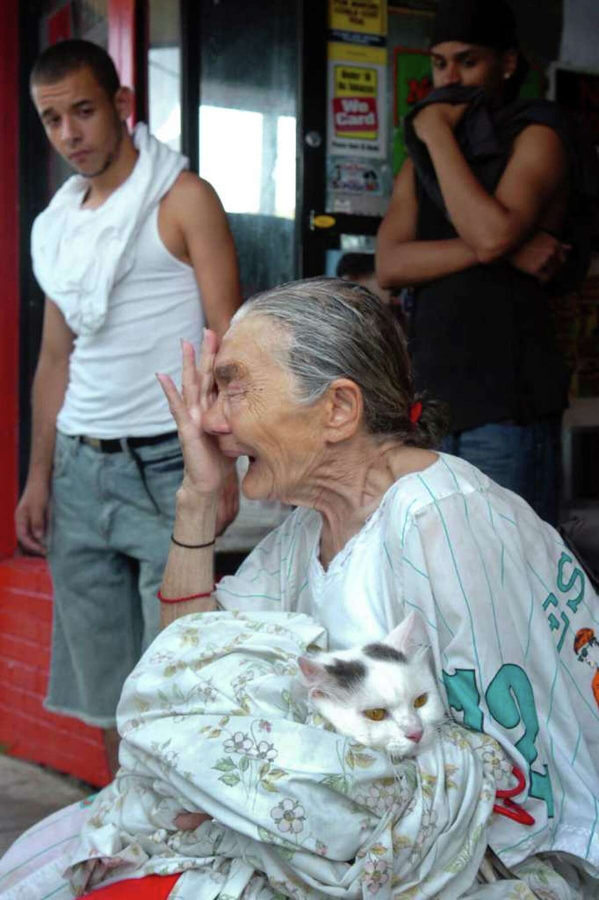 Luz Acevero, 77, holds her cat Papito and cries in front of her apartment building at 503-519 East Main St., in Bridgeport, Conn. Monday June 28th, 2010. The roof of the building was damaged in last Thursday's storm, and residents were evacuated Monday after it began to leak during a thunderstorm, raising concerns that it might collapse.