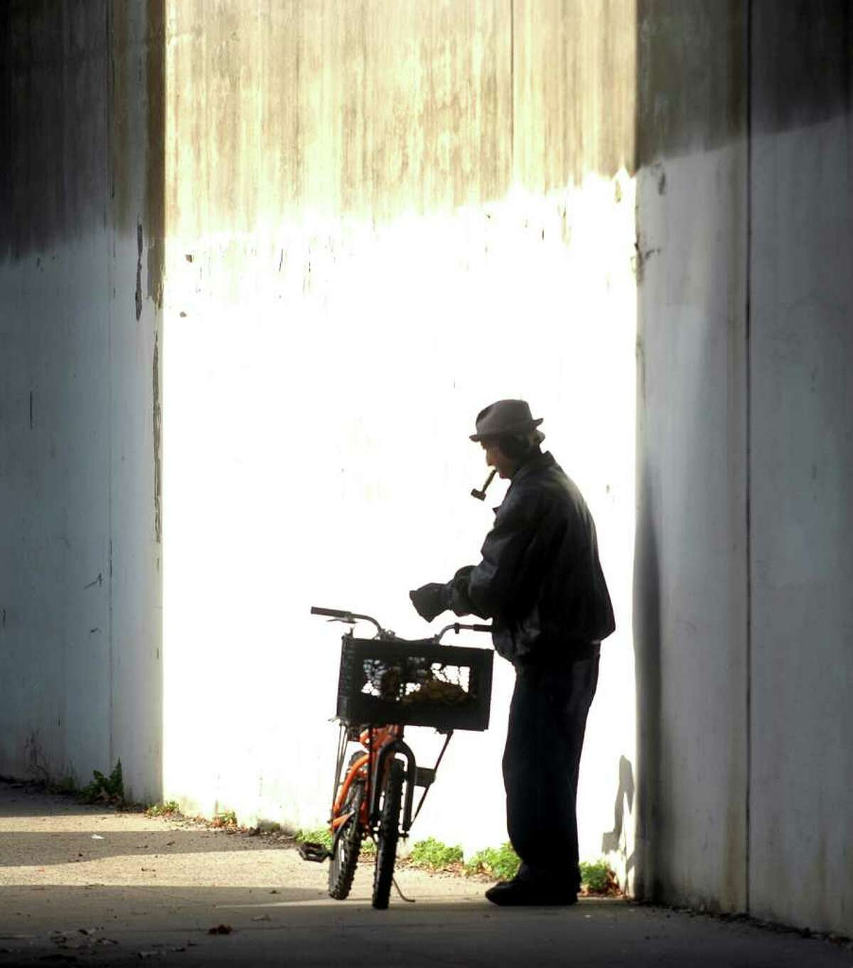 A man stops to light his pipe before he continues along State Street in Bridgeport Conn. on Friday November 19, 2010.