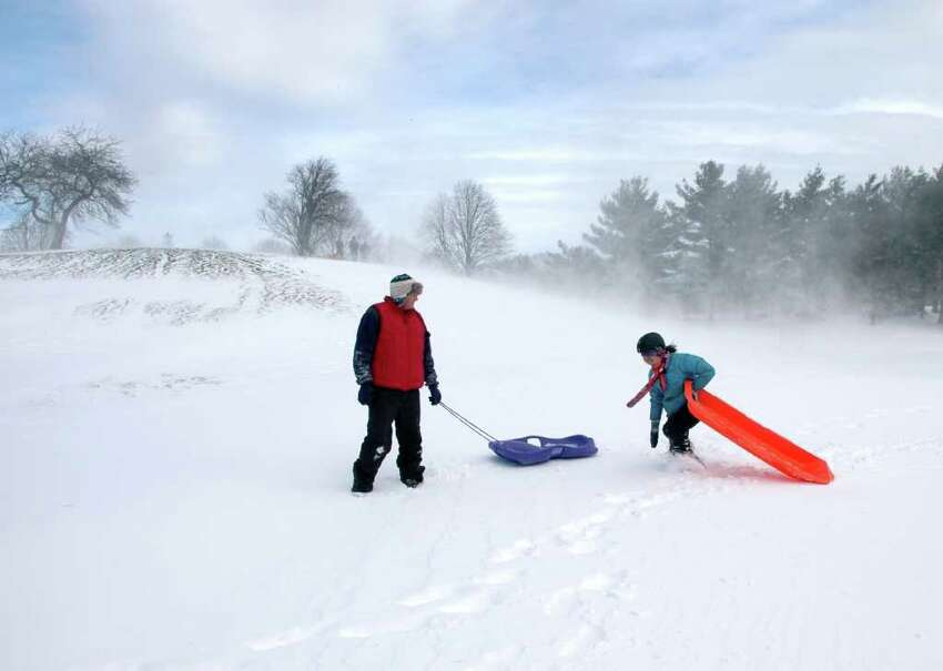 Paul Rivenberg and his daughter Julie head home after some morning sledding at Fairfield University on Monday December 27, 2010.