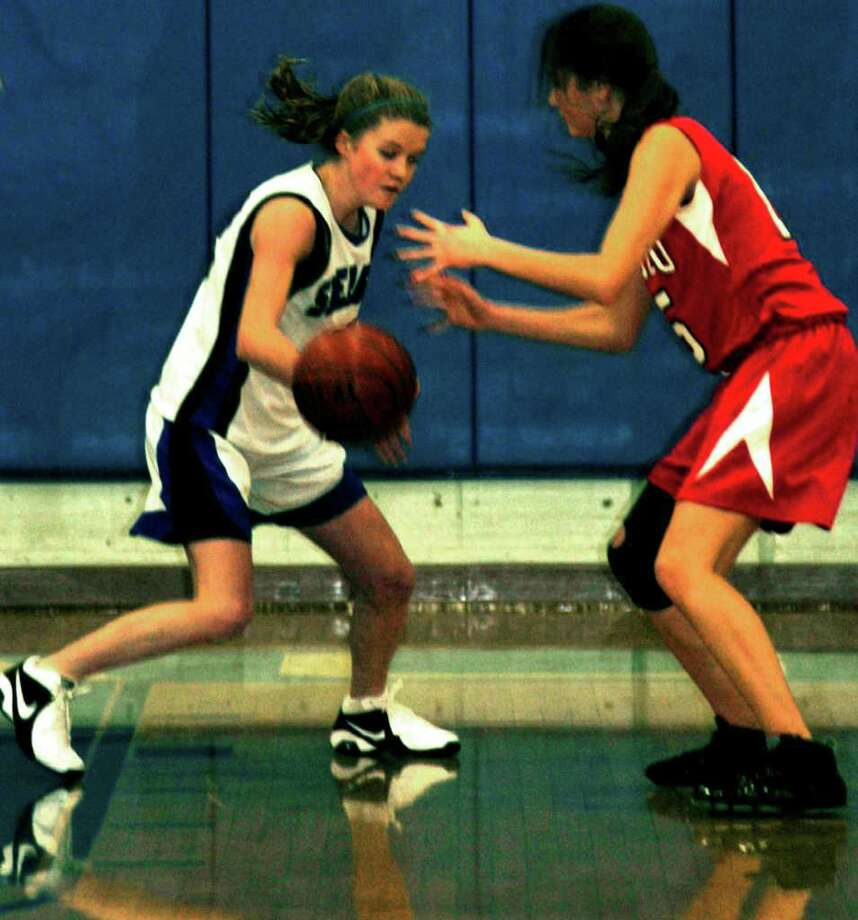 The quick hands of Linnea Quist, left, of the Spartans leaves a Wamogo rival with that empty-handed feeling during Tuesday's hardcourt duel at Shepaug.  Spectrum/Dec. 28, 2010 Photo: Norm Cummings / The News-Times