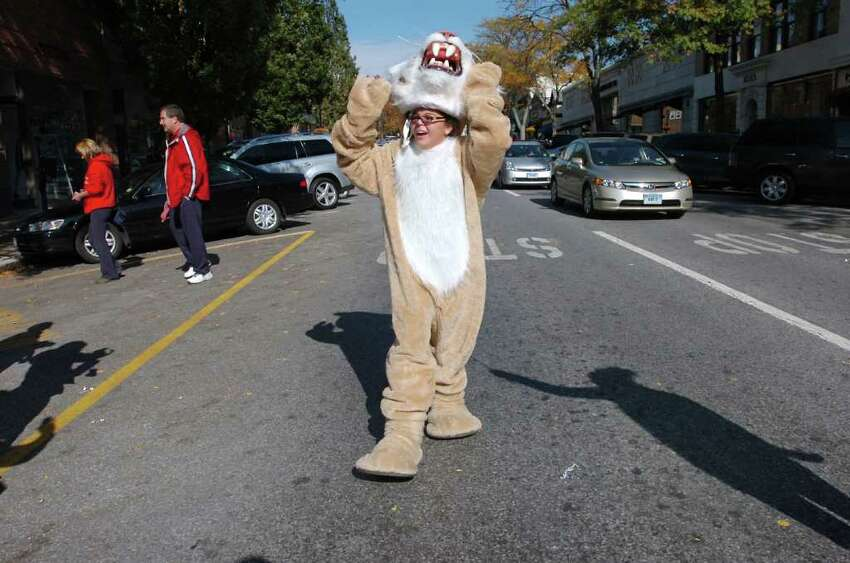 Raven Vaz, 11, a Western Middle School seventh grader, takes the head of her mascot's costume during the Greenwich High School homecoming parade on Greenwich Avenue, Saturday morning, Oct. 23, 2010. Vaz was the last person marching in the parade.