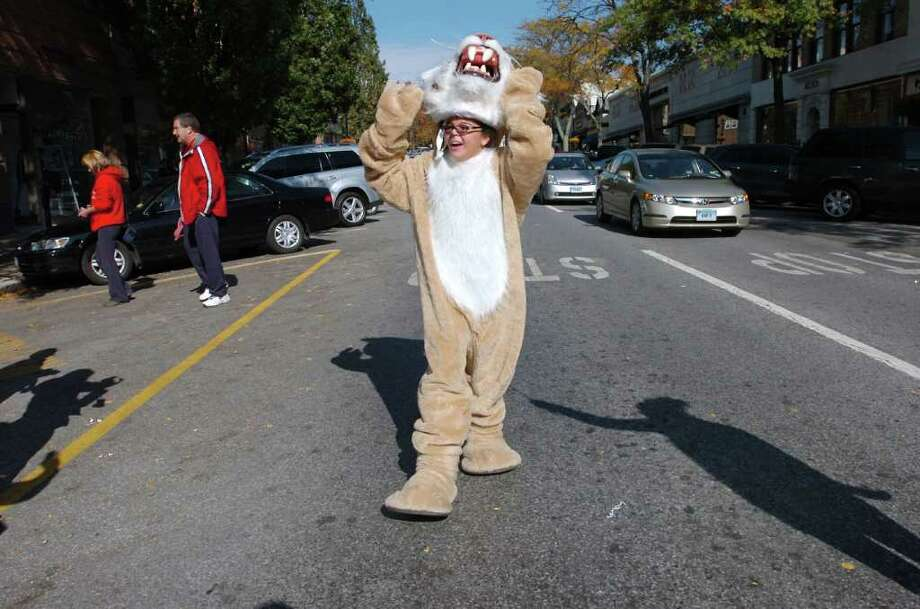 Raven Vaz, 11, a Western Middle School seventh grader, takes the head of her mascot's costume during the Greenwich High School homecoming parade on Greenwich Avenue, Saturday morning, Oct. 23, 2010.  Vaz was the last person marching in the parade. Photo: Bob Luckey / Greenwich Time