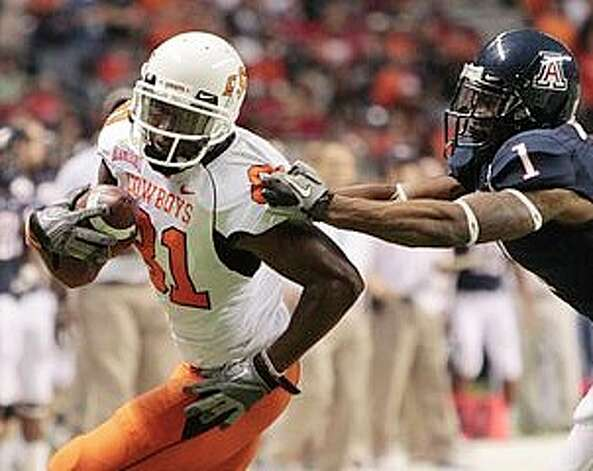 Oklahoma State's Justin Blackmon (left) tries to get away from Arizona's Robert Golden after a catch. Photo: Eric Gay/Associated Press