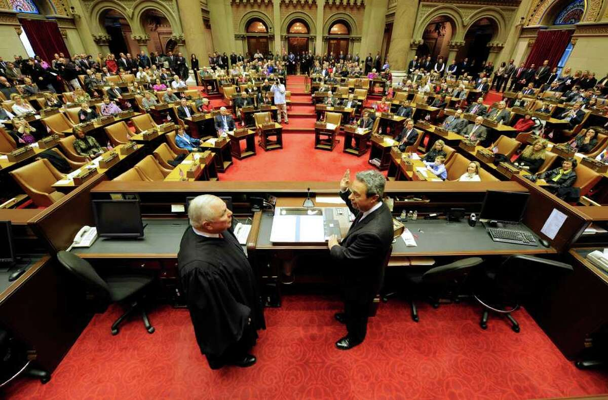 The Assembly chamber won?t be the focus of attention for the State of the State next week, but it was Wednesday as state Supreme Court Presiding Justice Anthony V. Cardona, left, swears in Assemblyman Ron Canestrari of Cohoes and other top Democrats. (Skip Dickstein/ Times Union)