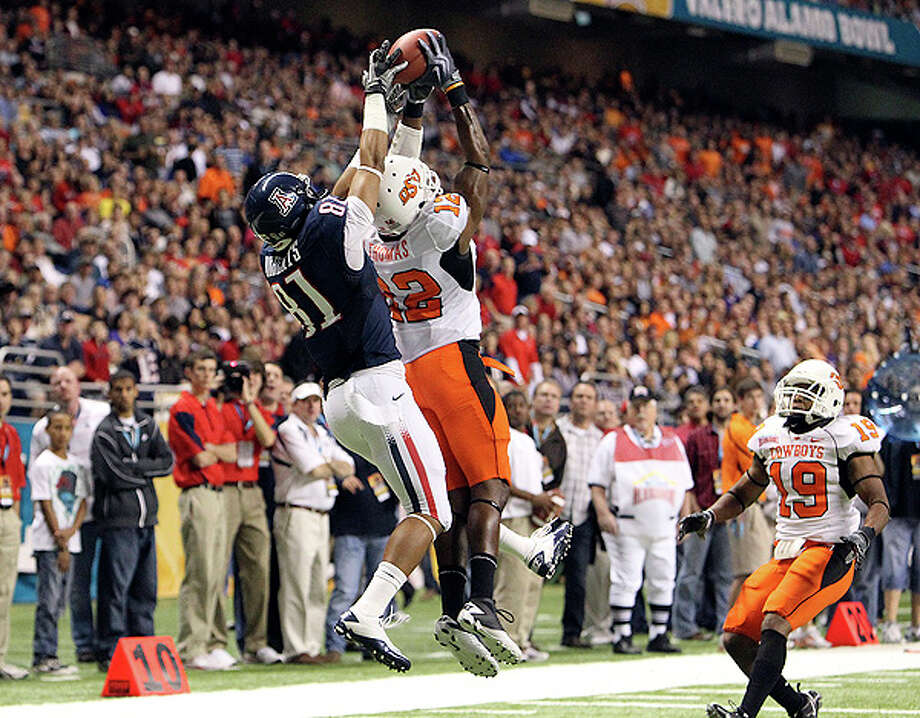 Oklahoma State's Johnny Thomas (12) intercepts a pass against Arizona's Dave Roberts (81) in the first half at the 2010 Valero Alamo Bowl at the Alamodome in San Antonio on Wednesday, Dec. 29, 2010. Kin Man Hui/kmhui@express-news.net Photo: KIN MAN HUI, SAN ANTONIO EXPRESS-NEWS / kmhui@express-news.net
