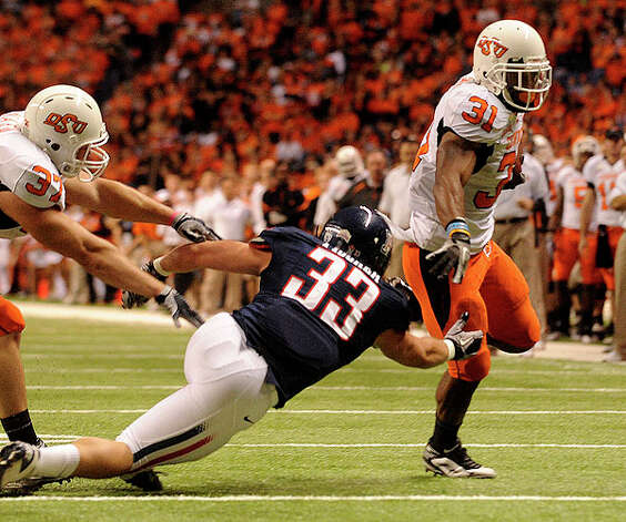 Oklahoma State's Jeremy Smith eludes Arizona defender Jake Fischer to score a first-half touchdown during the Valero Alamo Bowl in the Alamodome on Wednesday, Dec. 29, 2010. BILLY CALZADA / gcalzada@express-news.net Photo: BILLY CALZADA, SAN ANTONIO EXPRESS-NEWS / gcalzada@express-news.net