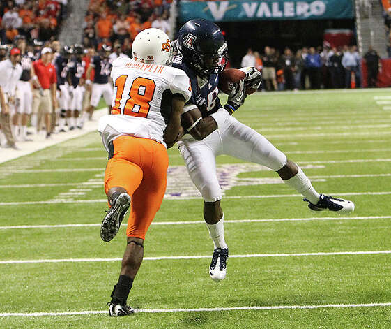 Arizona's Travis Cobb (06) makes a catch against Oklahoma State's Devin Hedgepeth (18) in the first half at the 2010 Valero Alamo Bowl at the Alamodome in San Antonio on Wednesday, Dec. 29, 2010. Cobb was called for a pass interference on the play. Kin Man Hui/kmhui@express-news.net Photo: KIN MAN HUI, SAN ANTONIO EXPRESS-NEWS / kmhui@express-news.net