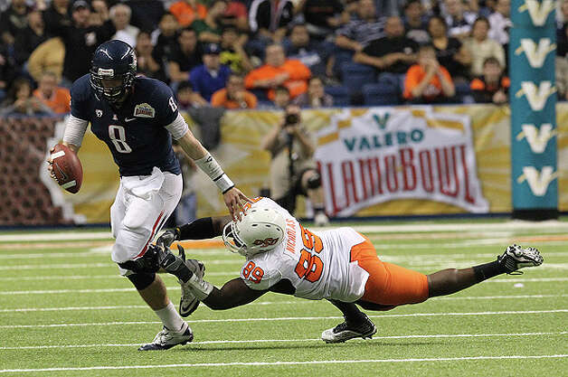 Oklahoma State's Nigel Nicholas (89) attempts a tackle against Arizona quarterback Nick Foles (08) in the first half at the 2010 Valero Alamo Bowl at the Alamodome in San Antonio on Wednesday, Dec. 29, 2010. Kin Man Hui/kmhui@express-news.net Photo: KIN MAN HUI, SAN ANTONIO EXPRESS-NEWS / kmhui@express-news.net