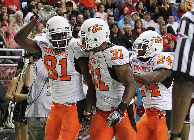 Oklahoma State's Justin Blackmon (81) gets congratulated by teammates Jeremy Smith (31) and Kendall Hunter (24) after Blackmon scored his second touchdown against Arizona at the 2010 Valero Alamo Bowl in the second half at the Alamodome in San Antonio on Wednesday, Dec. 29, 2010. Kin Man Hui/kmhui@express-news.net Photo: KIN MAN HUI, SAN ANTONIO EXPRESS-NEWS / kmhui@express-news.net