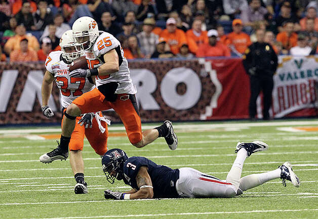 Oklahoma State's Josh Cooper (25) leaps over Arizona's Anthony Wilcox (03) during a run at the 2010 Valero Alamo Bowl in the second half at the Alamodome in San Antonio on Wednesday, Dec. 29, 2010. Kin Man Hui/kmhui@express-news.net Photo: KIN MAN HUI, SAN ANTONIO EXPRESS-NEWS / kmhui@express-news.net