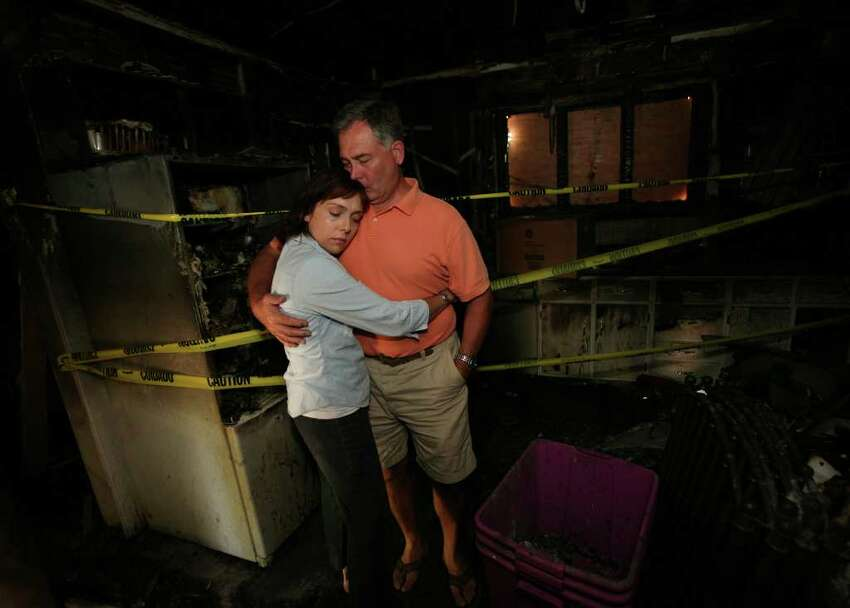 Anna and Eric Pelletier share a hug in the kitchen of their home at 46 Senior Place in Fairfield. The house was destroyed in a fire on Friday in which their two dogs perished.