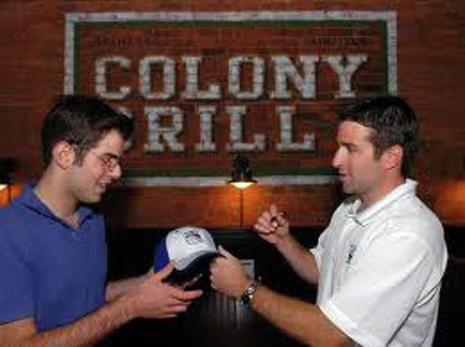 Rangers captain Chris Drury, right, signs an autograph for a fan at the Colony Grill's operning earlier this year. Drury is a co-owner of the pizza parlor and brought a film crew and some teammates by in November to tape a feature for the New York Rangers pre-game show that will air Saturday at 7 p.m. on the Madison Square Garden network. Photo: File Photo / Fairfield Citizen