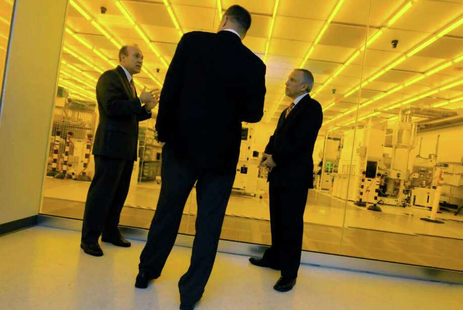 Illuminated by the yellow lights of a clean room Michael M. Fancher , University at Albany V.P. for Buisness Developement & Economic Outreach ,left, gives a tour of the Albany NanoTech to U.S.Congressman Chris Gibson ,center, with Steve Janack, University at Albany  V.P. for Marketing and Communication in Albany 12/30/2010.( Michael P. Farrell/Times Union ) Photo: Michael P. Farrell