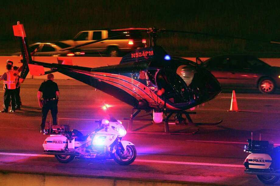 A police helicopter makes an emergency landing on U.S. 281 at Nakoma Street, just southwest of the San Antonio International Airport Thursday night. Photo: TOM REEL, SAN ANTONIO EXPRESS-NEWS / © 2010 San Antonio Express-News