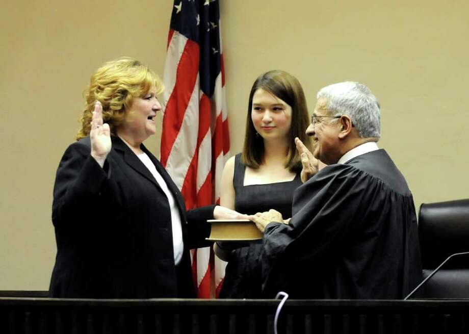 Jennifer Jensen-Bergan, left, is sworn in as Saratoga County Family Court Judge on Thursday, Dec. 30, 2010, at Saratoga County Supreme Court in Ballston Spa. Her daughter Mckenzie Bergan, center, holds the Bible as state Judge Stephen A. Ferradino conducts the ceremony. Jensen-Bergan is the first woman to be elected to a judgeship in the county's history (Cindy Schultz / Times Union) Photo: Cindy Schultz