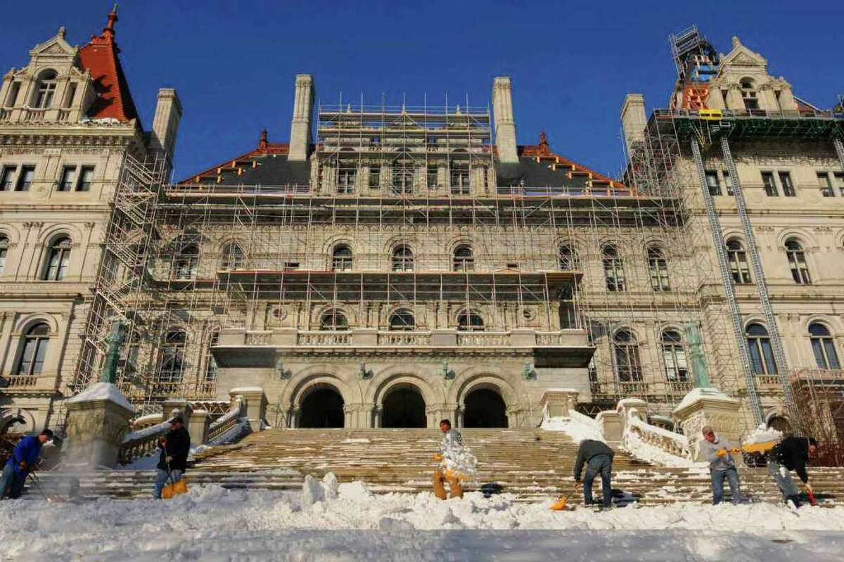 OGS employees clear off the front steps of the Capitol. Andrew Cuomo will be sworn in as governor on Saturday, New Year's Day.( Michael P. Farrell/Times Union )
