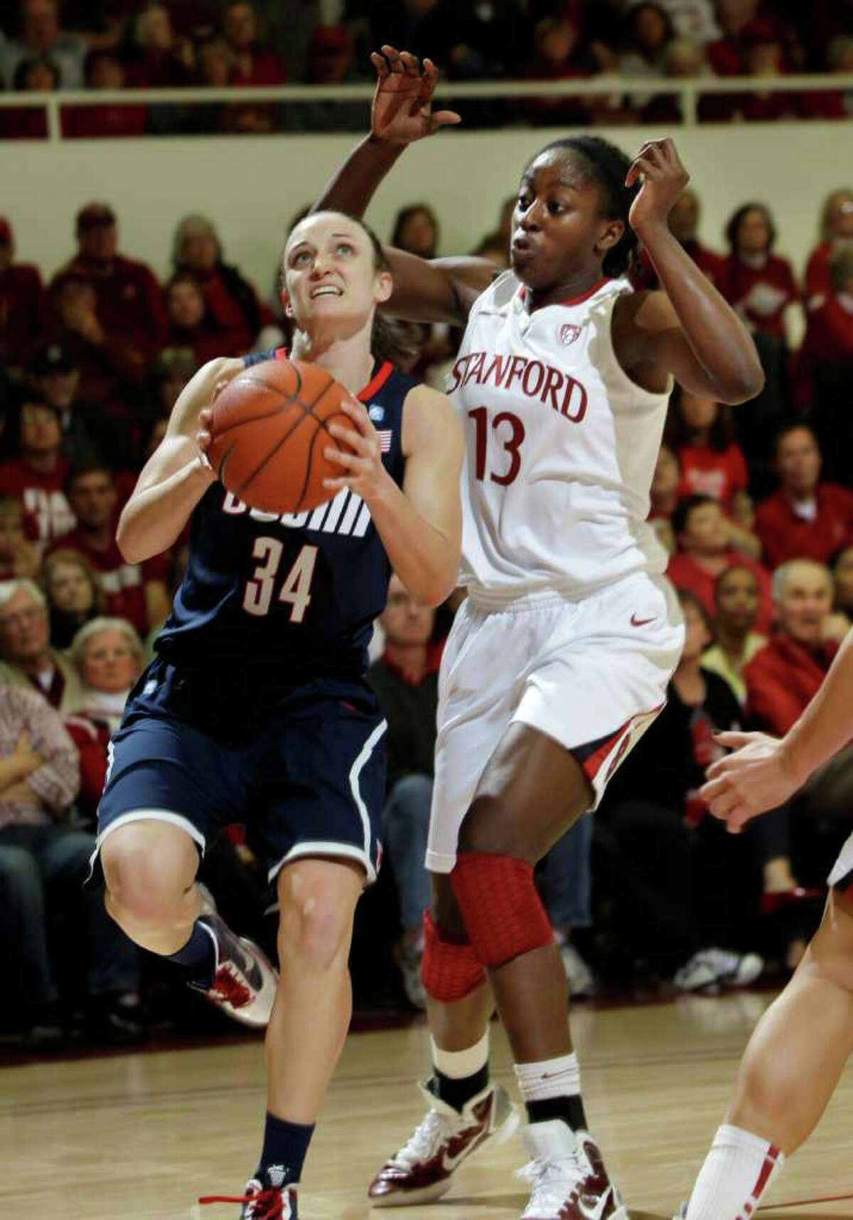Connecticut guard Kelly Faris (34) goes to the basket in front of Stanford forward Chiney Ogwumike (13) in the first half of an NCAA college basketball game in Stanford, Calif., Thursday, Dec. 30, 2010. (AP Photo/Paul Sakuma)