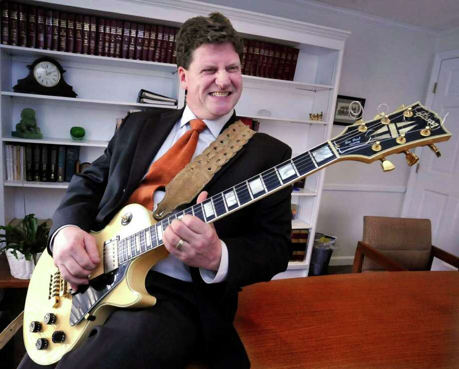 Attorney Liam Glynn, 45, of Danbury, plays his 81' Les Paul Custom guitar in his Danbury law office, on Tuesday, Feb.2,2010. Photo: Michael Duffy / The News-Times