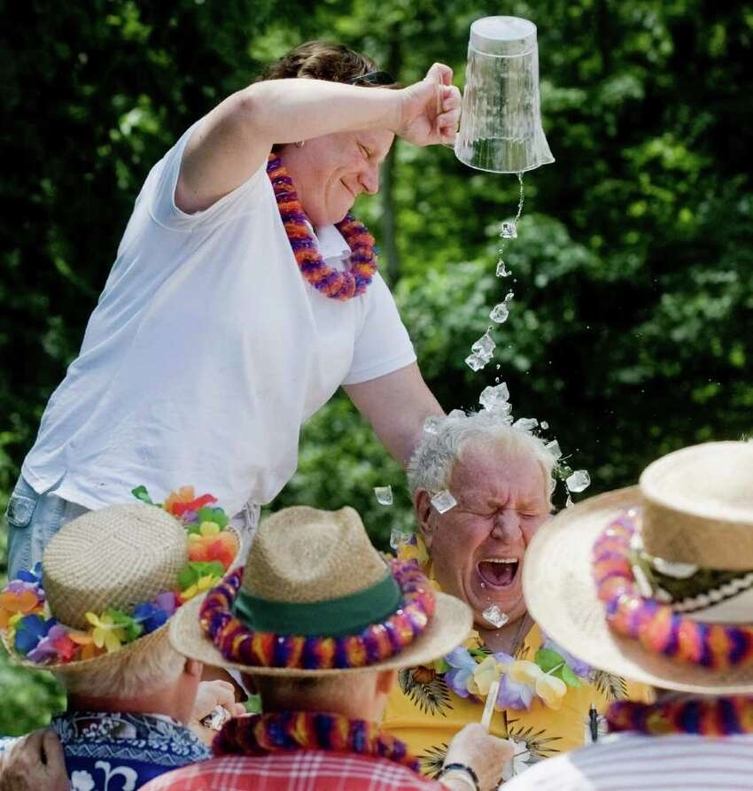 Assistant Parks and Rec director Robin Matthews cools off 81-year old Frank Lancaster of Ridgefield during the Senior Citizen Luau at Great Pond, sponsored by Ridgefield's Parks and Recreation Department. Photo taken Tuesday, July 27, 2010