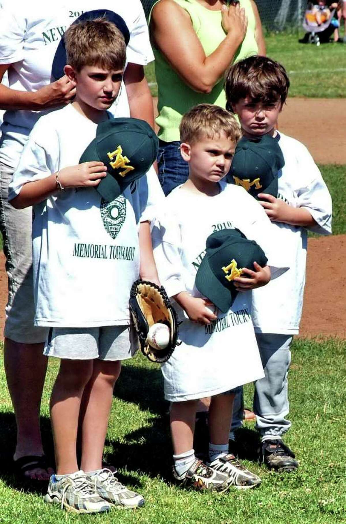 Matthew Hassiak, 8, DJ Hassiak, 4, and Luke Hassiak, 6, say the Pledge of Allegiance, after throwing the first pitch at the New Milford Youth Baseball/Softball Tournament, on Saturday, June 19, 2010. The first pitch was in honor of their father, Danbury police officer, Donald Hassiak, who was killed by a hit and run driver while riding his bike to work.