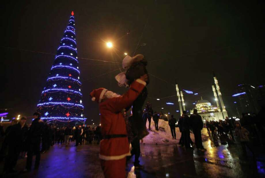 A man dressed as Grandfather Frost, Russian Santa Claus, holds a child  in downtown Grozny, Chechnya, southern Russia, Friday,  Dec. 31, 2010, with a New Year tree and a mosque in the background.  New Year, which is the biggest holiday of the year in Russia, is also very popular in predominantly Muslim Russian region of Chechnya. (AP Photo/Musa Sadulayev) Photo: Musa Sadulayev / AP