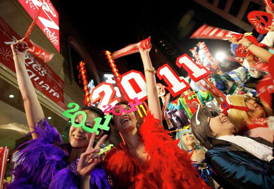 Revellers wave during the New Year's Eve celebrations in Hong Kong's Times Square, Saturday, Jan. 1, 2011. (AP Photo/Vincent Yu) Photo: Vincent Yu / AP