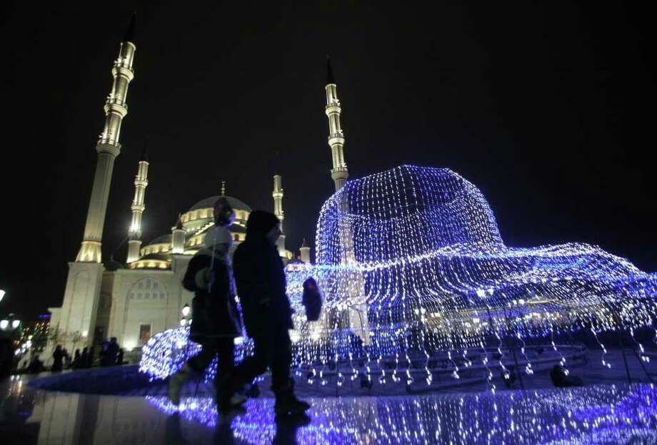 Prople pass by city decorations and a mosque, at rear left, in downtown Grozny, Chechnya, southern Russia, Friday Dec. 31, 2010. New Year, which is the biggest holiday of the year in Russia, is also very popular in predominantly Muslim Russian region of Chechnya. (AP Photo/Musa Sadulayev) Photo: Musa Sadulayev / AP