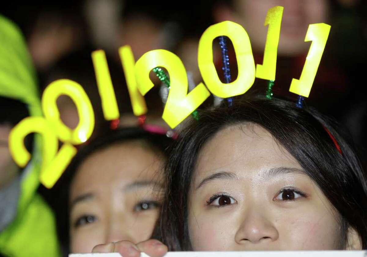South Korean women wear signs of 2011 during New Year celebrations in Seoul, South Korea, Saturday, Jan. 1, 2011. (AP Photo/ Lee Jin-man)