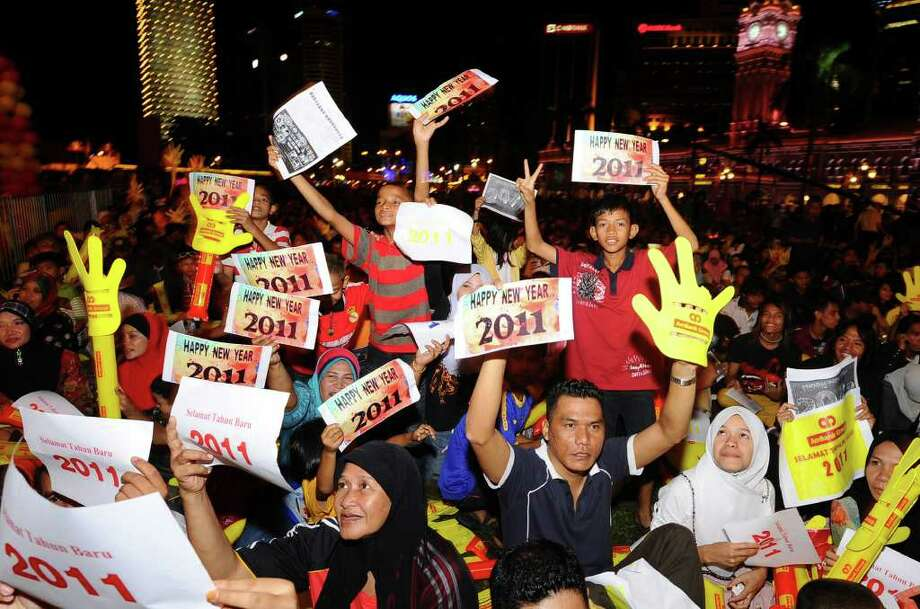 "Malaysian people hold placards reading ""Happy New Year 2011"" during New Year's Eve celebrations in downtown Kuala Lumpur, Malaysia, Friday, Dec. 31, 2010. (AP Photo) MALAYSIA OUT / AP"