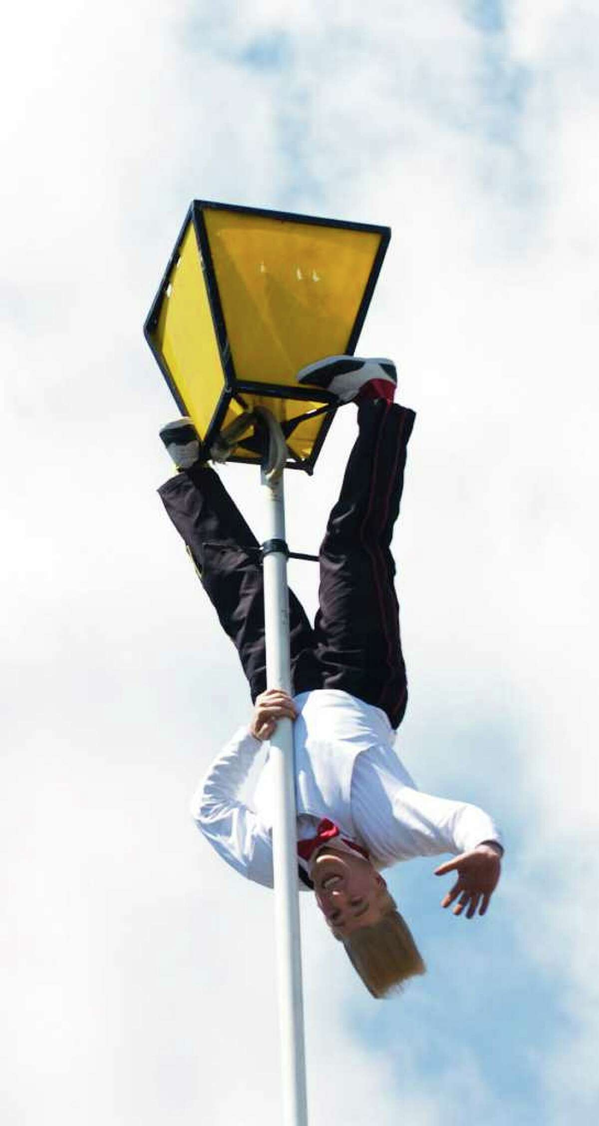 Bello Nock, the most famous daredevil clown, and star of the Big Apple Circus hangs upside down as he performs a stunt atop a 92 foot pole in Columbus Park on Tuesday May 4, 2010 in Stamford, Conn. The performance was to promote the Big Apple Circus' 32nd allñnew show, Bello is Back! as it makes its first ever appearance under the Big Top in Mill River Park from July 9 through July 25.