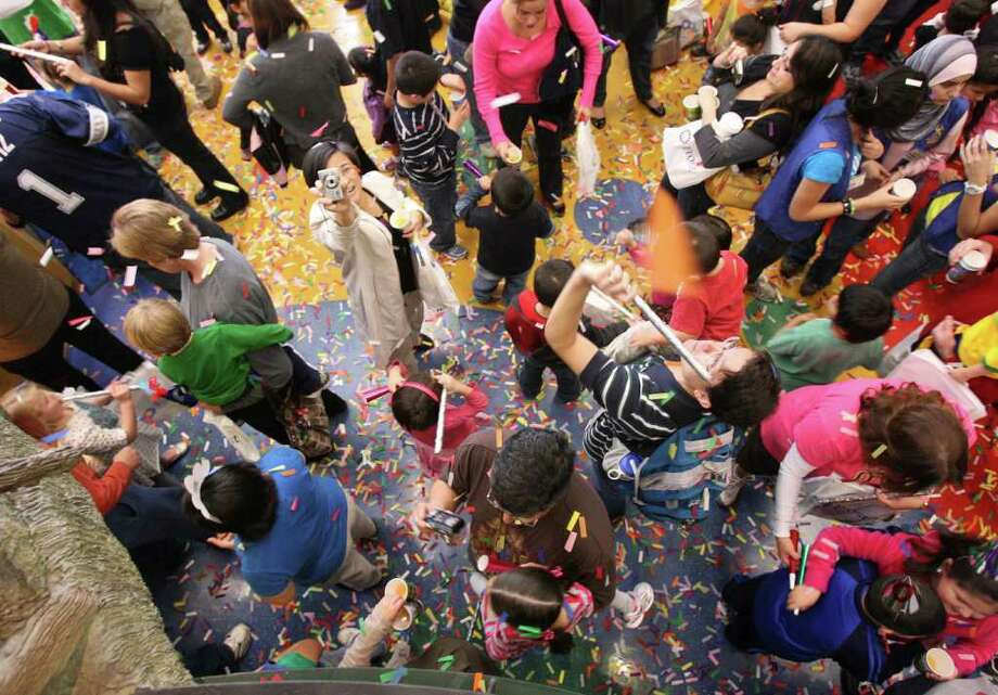 Kids celebrate at the Children's Museum after counting down to the unofficial start of 2011 at noon. The children made noisemakers and 2011 hats and received sparkling cider and flutter confetti. Eight hundred people attended the event. Photo: HELEN L. MONTOYA, SAN ANTONIO EXPRESS-NEWS / hmontoya@express-news.net