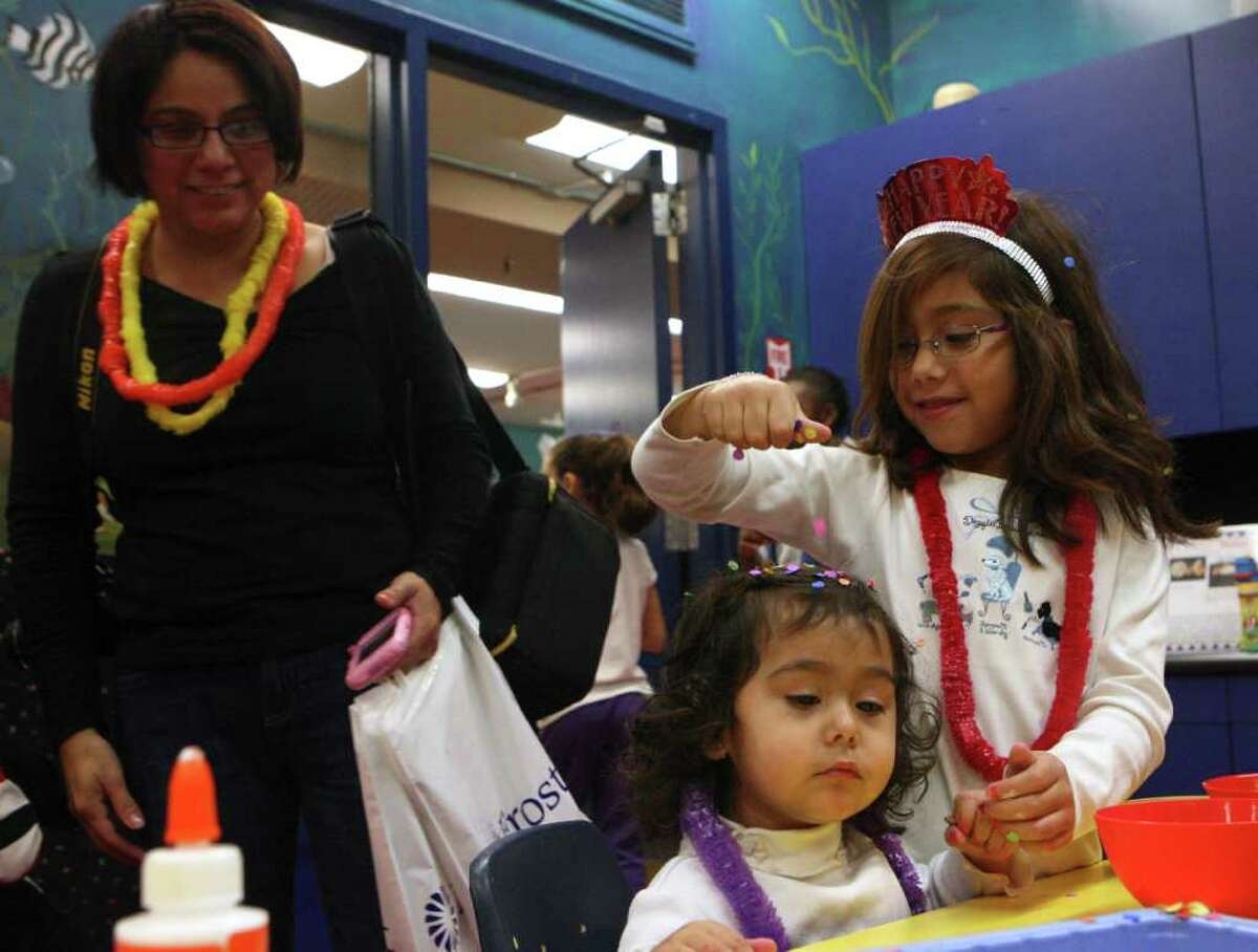 METRO: Abby Gonzales, 6, sprinkles confetti on her sister, Lexie Gonzales, 2, as their mom Norma looks on at the Children's Museum on Friday Dec. 31, 2010. Kids at the Children's Museum kicked off 2011 with a Kid's Countdown at noon. The children made noisemakers and 2011 hats before counting down at noon with sparkling cider and flutter confetti. 800 people attended the event. HELEN L. MONTOYA/hmontoya@express-news.net