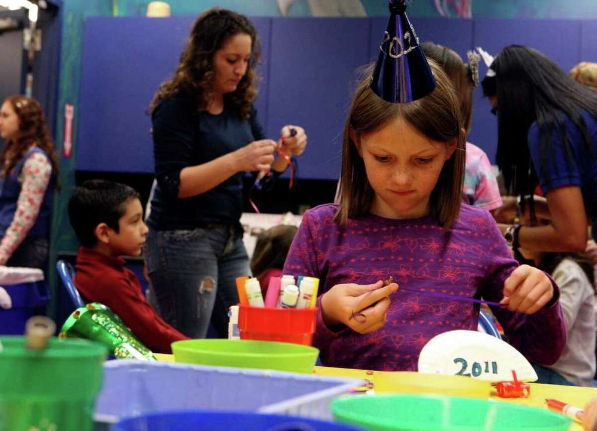 METRO: Kara Burkholder, 9, makes a noisemaker at the Children's Museum on Friday Dec. 31, 2010. Kids at the Children's Museum kicked off 2011 with a Kid's Countdown at noon. The children made noisemakers and 2011 hats before counting down at noon with sparkling cider and flutter confetti. 800 people attended the event. HELEN L. MONTOYA/hmontoya@express-news.net