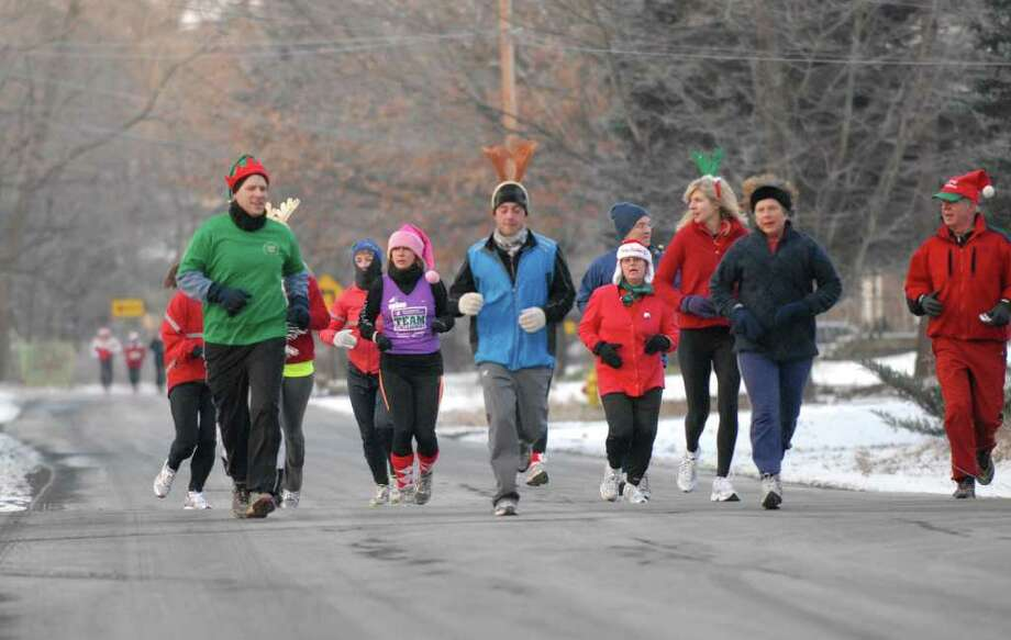 Lois Green, left in purple vest, takes part in an early morning Sunday run along Adams Place in Delmar with friends from a Delmar running group who she credits with helping her return to running after being diagnosed with cancer, Sunday morning December 19, 2010. (Will Waldron / Times Union) Photo: Will Waldron / 00011451A