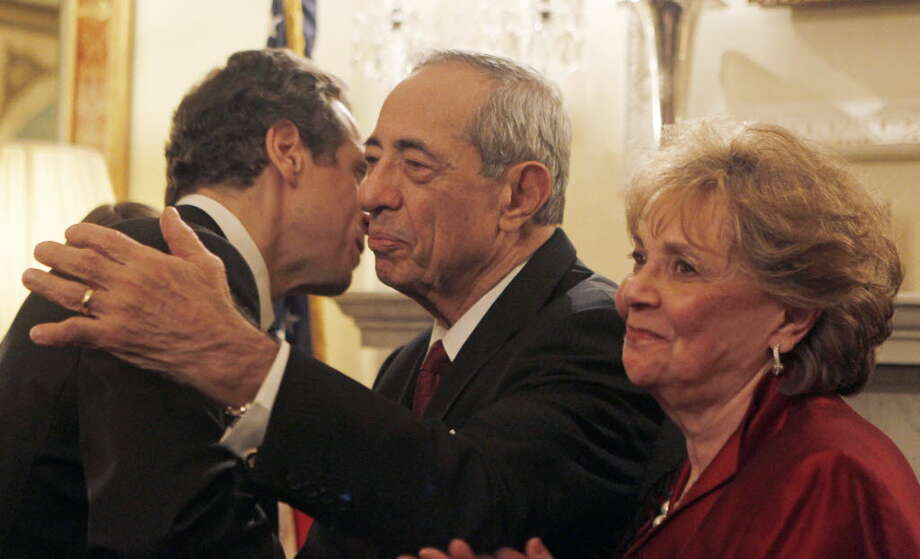 Gov. Andrew Cuomo, left, is congratulated by his parents, former Gov. Mario Cuomo, center, and mother Matilda, during a private swearing-in ceremony at the Executive Mansion in Albany on Friday, Dec. 31, 2010. (AP Photo/Mike Groll)