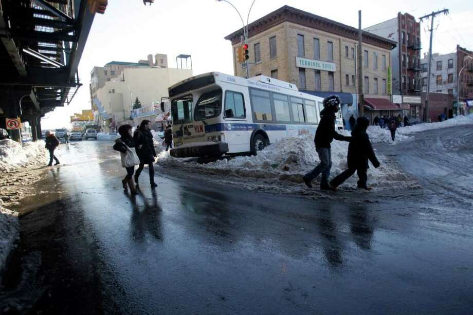 MTA bus service is getting back in operation, New York City officials say, after coaches were marooned in the storm, including this unit stuck in the middle of Stillwell Avenue in the Coney Island neighborhood in Brooklyn.  (AP Photo/Mary Altaffer) Photo: Mary Altaffer / AP